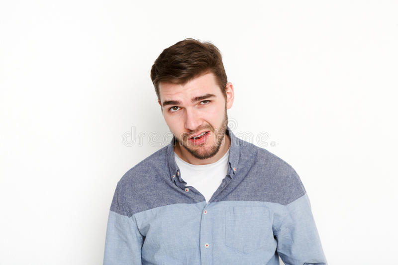Cocky man grimacing, portrait. Portrait of young daring guy with sassy look, isolated on white background stock images