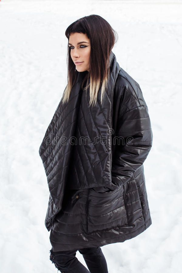 Cocky model close-up in snow looking aside. She is wearing black baggy jacket royalty free stock photo