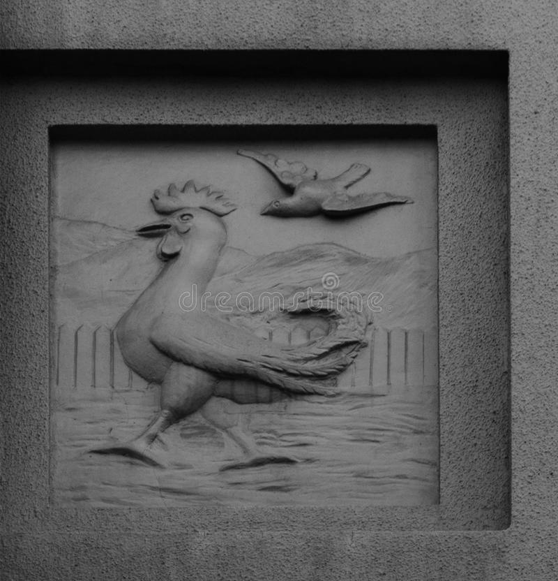 The cocky rooster. Shot in black and white, detail on the sculpture on the facade of this historic building representing some animals. Set in Logroño, La stock photography