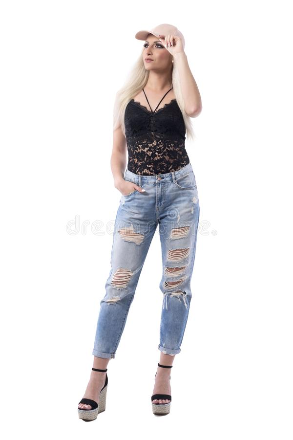 Cocky serious blonde hair woman in blue jeans and trendy cap holding visor looking up. Full body isolated on white background royalty free stock images