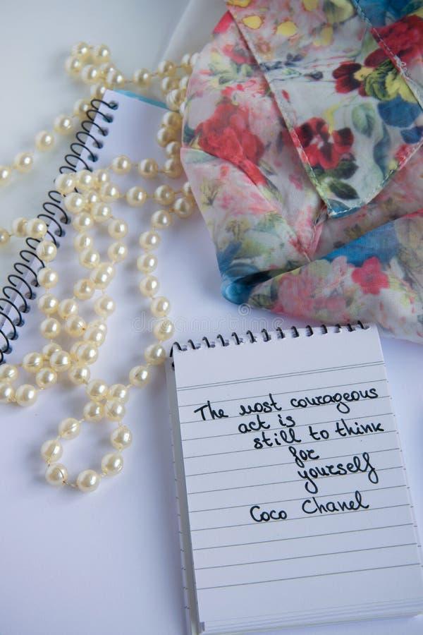 Coco Chanel zitiert geschrieben auf eine Blockanmerkung, Perlenzusätze und ein seidiges Blumenhemd lizenzfreie stockfotografie