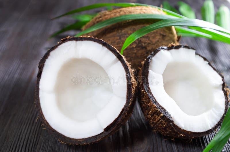 Coco cortado inteiro e meio maduro no fundo de madeira fotos de stock