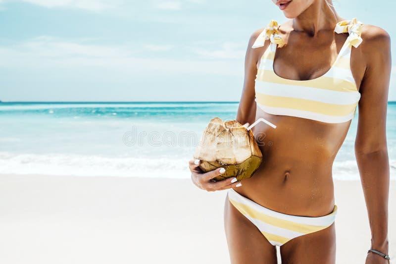 Coco de consumición de la mujer en la playa tropical imagen de archivo