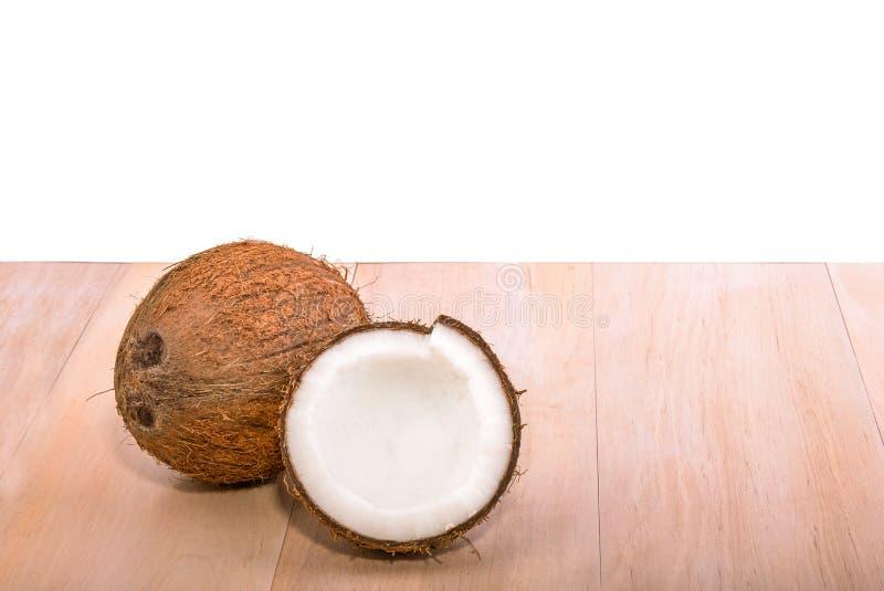Coco fresco, orgânico, marrom próximo em uma tabela de madeira clara, isolada em um fundo branco Um coco inteiro saboroso Fruta e imagens de stock