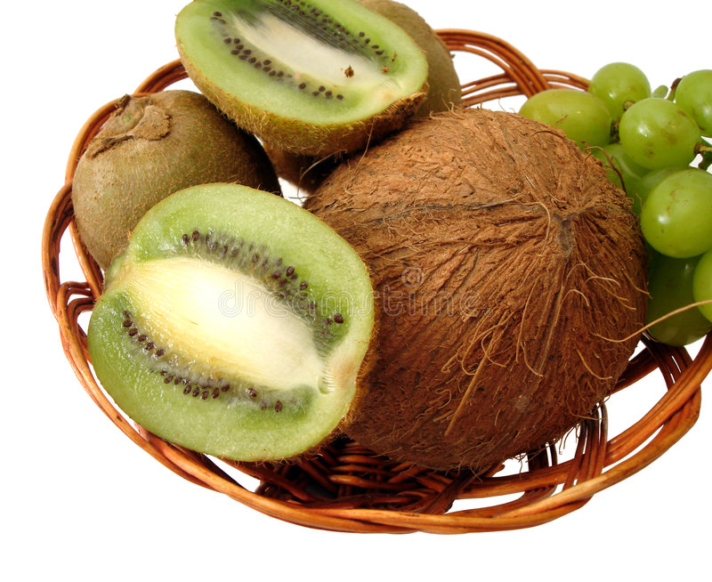 Coco, green kiwi and grapes in basket over white background royalty free stock photography