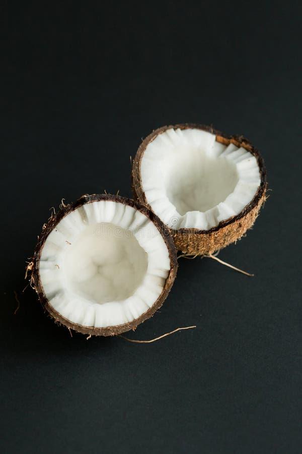 Coco maduro quebrado en fondo negro Carne blanca foto de archivo libre de regalías