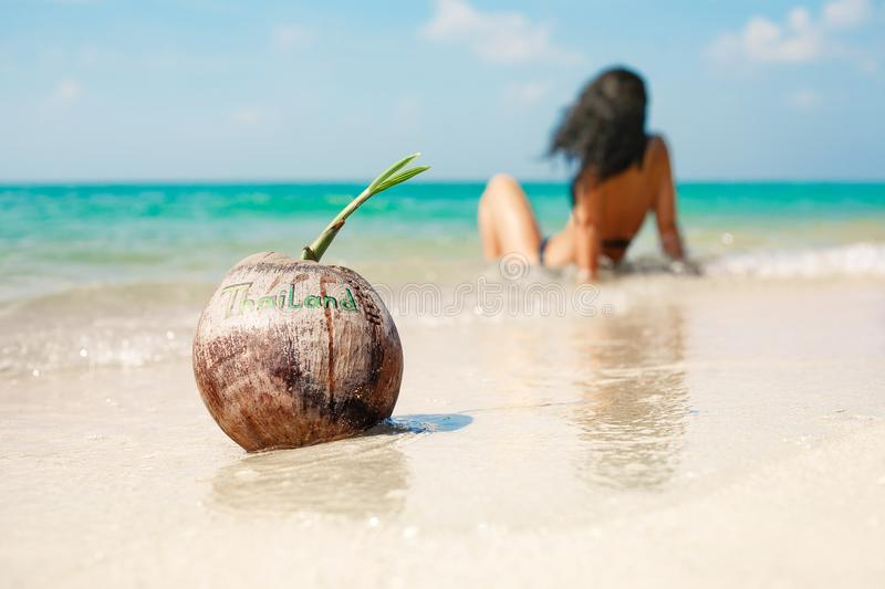 Coco na ilha tropical com a moça no biquini no backgrou fotografia de stock