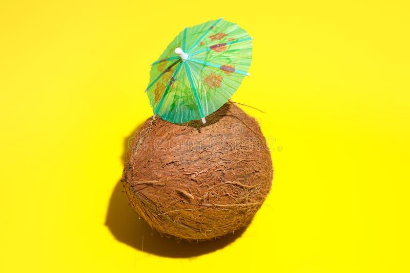 Coco natural fresco com um guarda-chuva do cocktail isolado no fundo amarelo Conceito de comer e da fazer dieta saud?veis Conceit foto de stock