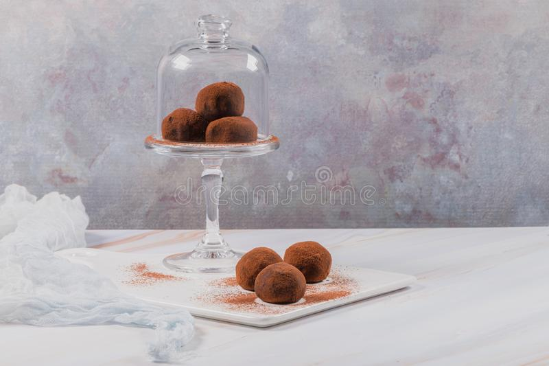 Chocolate balls cakes in a glass stand. Cocoa balls, chocolate balls cakes in a glass stand, sprinkled with cocoa powder royalty free stock photos
