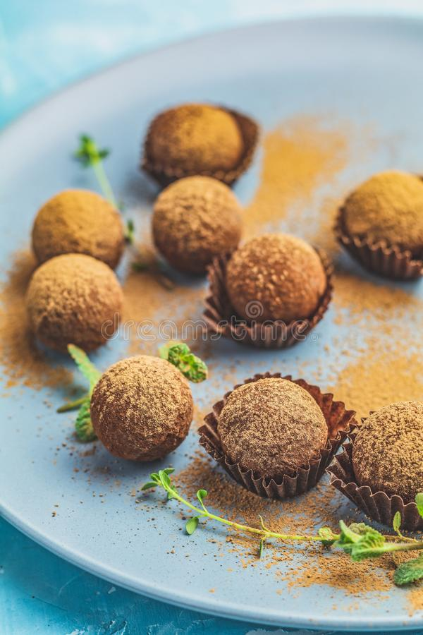 Cocoa balls, handmade chocolate balls cakes in a blue tray. Sprinkled with cocoa powder, fresh mint and thyme on dark blue concrete surface background. Close royalty free stock images