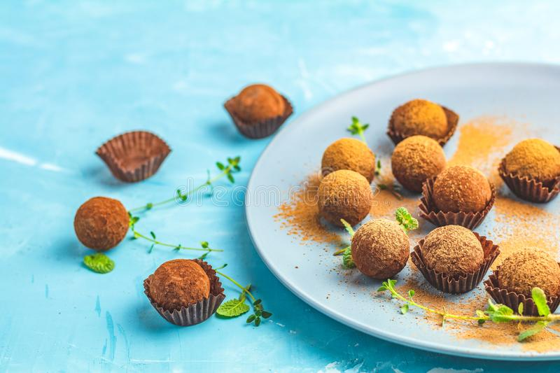 Cocoa balls, handmade chocolate balls cakes in a blue tray. Sprinkled with cocoa powder, fresh mint and thyme on dark blue concrete surface background. Close stock images