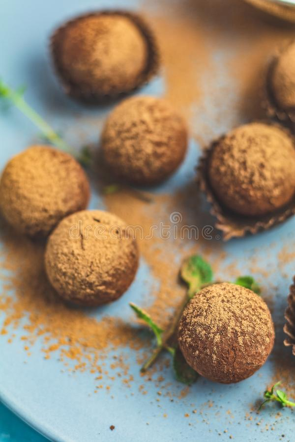 Cocoa balls, handmade chocolate balls cakes in a blue tray. Sprinkled with cocoa powder, fresh mint and thyme on dark blue concrete surface background. Close stock photography