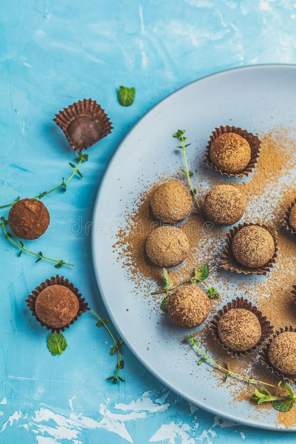 Cocoa balls, handmade chocolate balls cakes in a blue tray. Sprinkled with cocoa powder, fresh mint and thyme on dark blue concrete surface background. Close royalty free stock photography