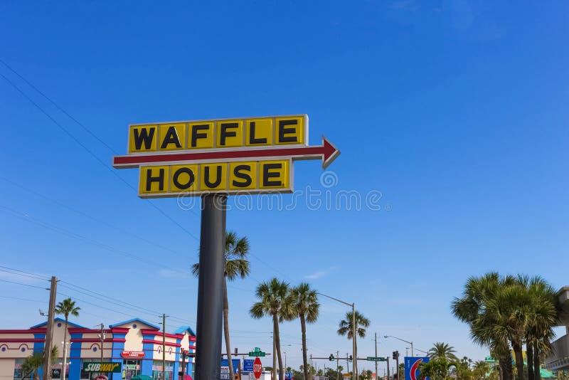 Cocoa Beach, FLORIDA, USA - April 28, 2018: The sign Waffle House against blue sky. Cocoa Beach, FLORIDA, USA - April 28, 2018: The road sign Waffle House royalty free stock photos