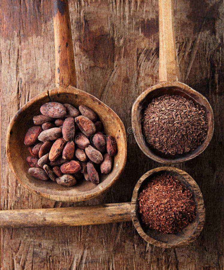 Cocoa beans, hot chocolate flakes and grated dark. Chocolate in old texured spoons bowls on wood stock photos