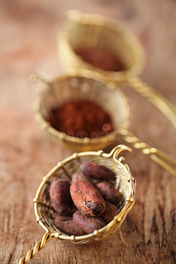 Cocoa beans in old rustic style silver sieves. On old wooden background stock photos