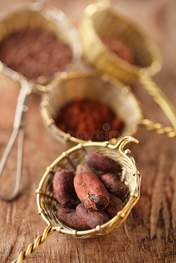 Cocoa beans in old rustic style silver sieves. On old wooden background royalty free stock photography