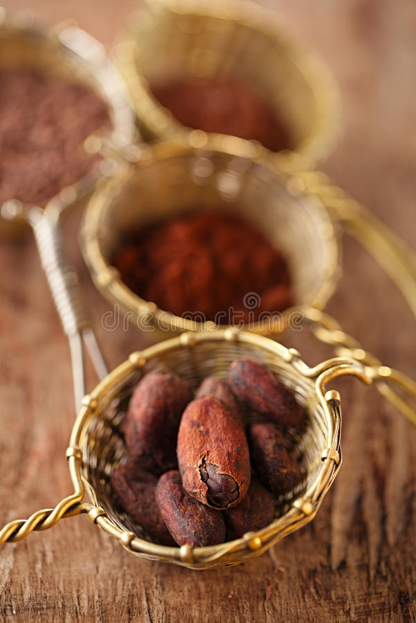 Cocoa beans in old rustic style silver sieves. On old wooden background stock photography