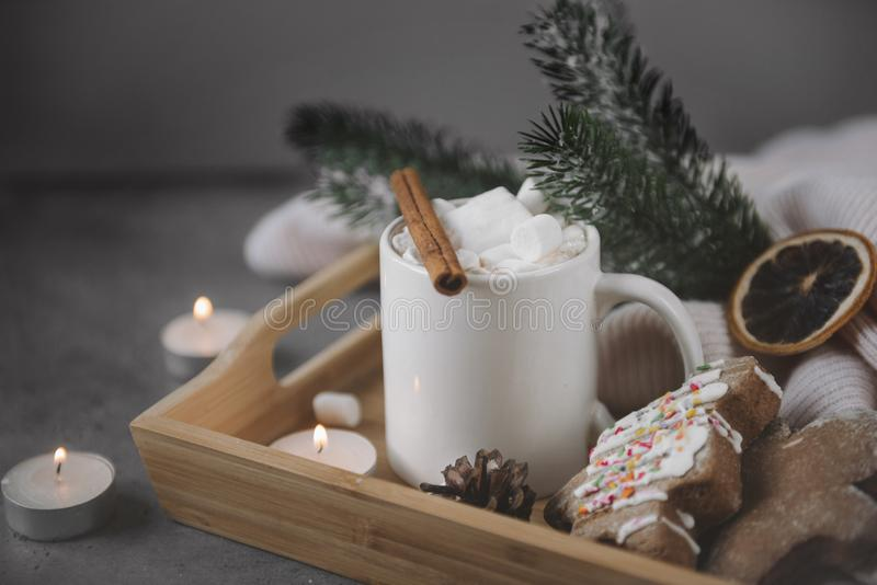 Cocoa with cinnamon and marshmallows, spruce branch, cookies on a tray, candles, a slice of dried orange, on a gray background, royalty free stock photography
