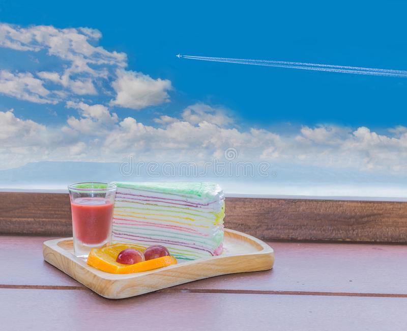 Cocoa, coffee, rainbow crepe, lemon, grape, on the wooden tray with the beautiful blue sky and cloud. Abstract soft focus cocoa, coffee, rainbow crepe, lemon royalty free stock photo