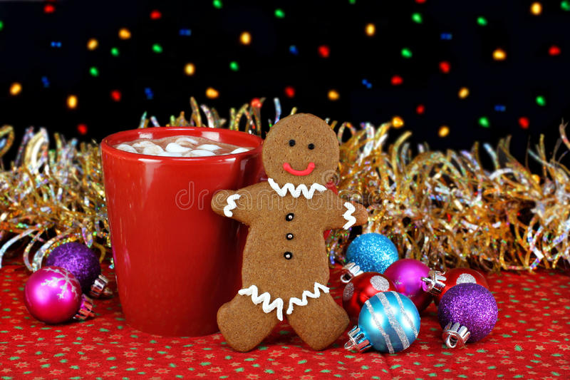 Cocoa and a gingerbread cookie. One cup of cocoa with marshmallows and a standing gingerbread man cookie in a night setting. Bokeh Christmas lights and ornaments stock image