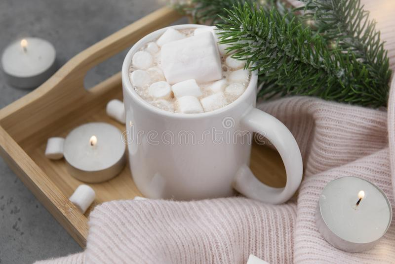 Cocoa, hot chocolate with marshmallows, spruce branch, candles with lights, pink knitted sweater on a tray on a gray stock photography