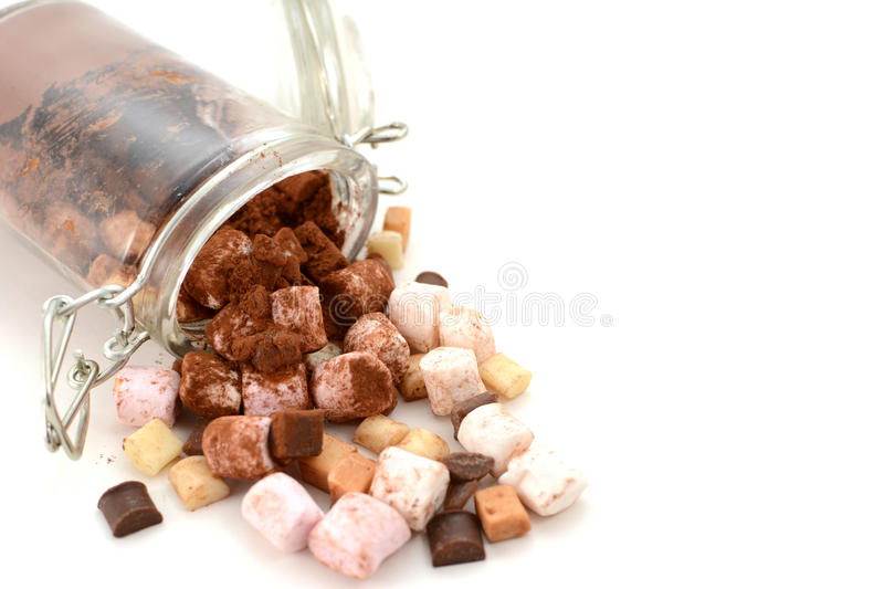 Cocoa and hot chocolate toppings spill from a jar. Cocoa and hot chocolate toppings spill from a glass jar with copy space on a white background royalty free stock photos