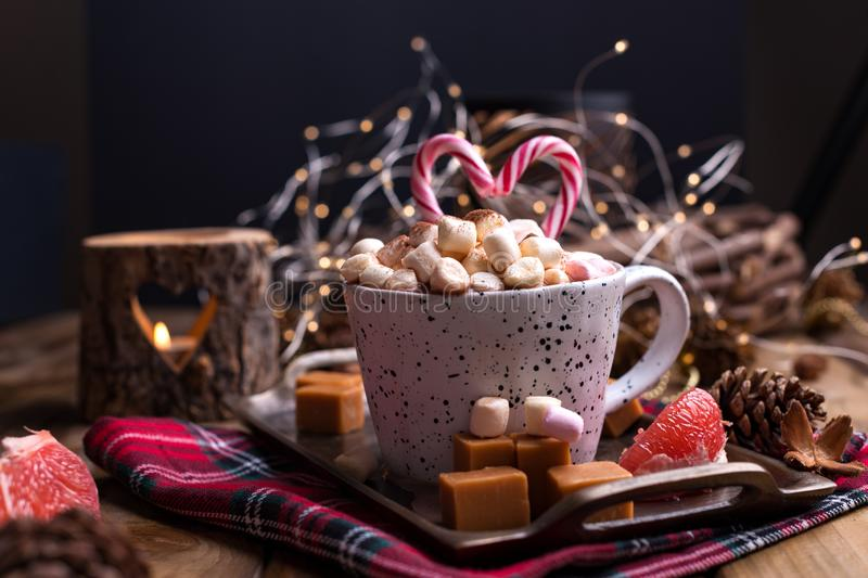 Cocoa with marshmallows in a white mug, different Christmas candies and sweets. Photo in dark style and free space for text. royalty free stock image