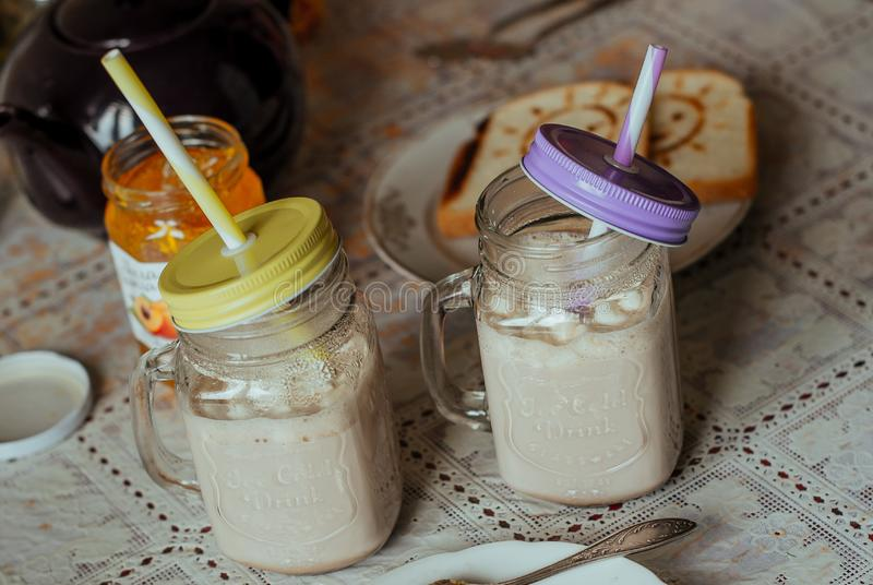 Cocoa with milk in jar and toasts at kitchen table royalty free stock photography