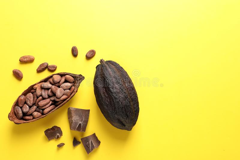 Cocoa pods with beans and chocolate pieces on yellow background, flat lay. Space for text royalty free stock photo