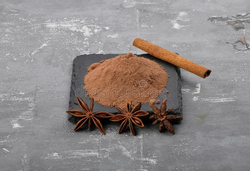 Cocoa powder, cinnamon stick and star anis on concrete. Colorful and crisp image of cocoa powder, cinnamon stick and star anis on concrete royalty free stock photos