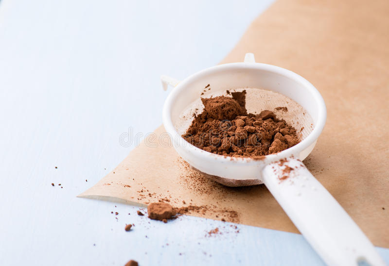 Cocoa powder in sieve. On baking paper, selective focus stock photo