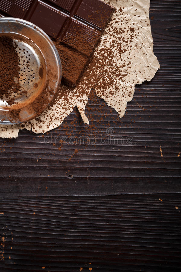 Cocoa powder with sieve on chocolate bar stock photo
