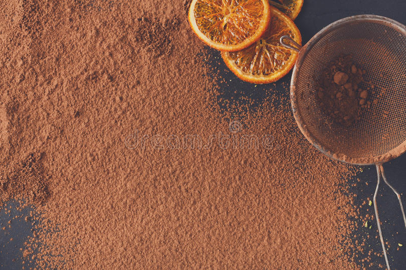 Cocoa powder in a sieve over black slate background. Sweet background. Cocoa powder in a sieve and sprinkled on surface, orange citrons and chocolate pieces on stock photos