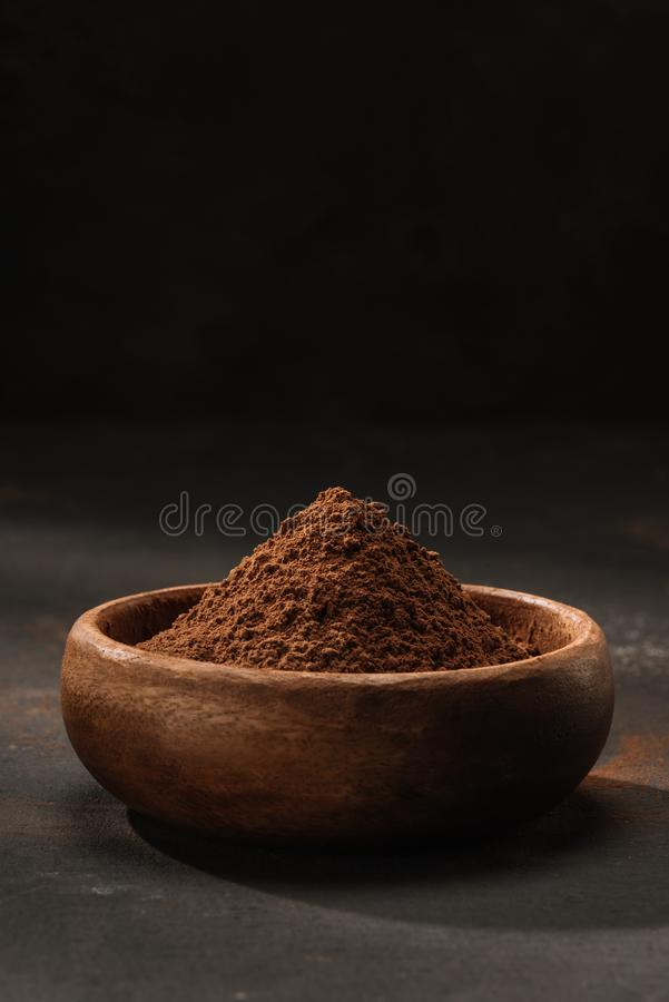 Cocoa powder in wooden bowl. On table royalty free stock photos