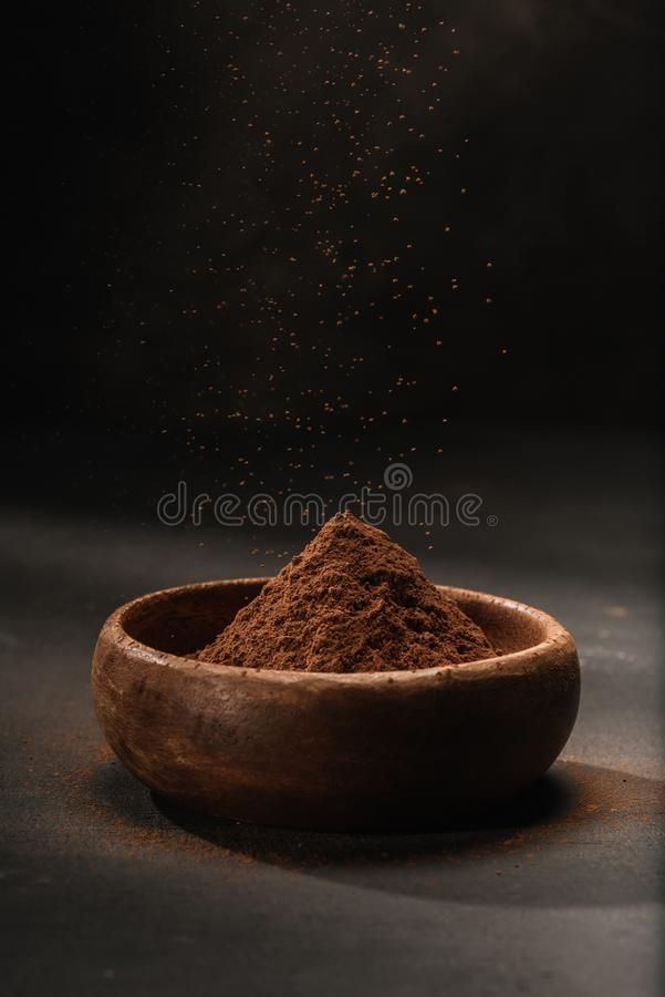 Cocoa powder in wooden bowl. On tabletop royalty free stock images