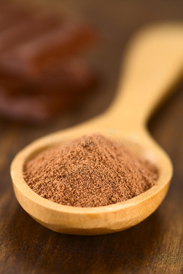 Cocoa Powder. On wooden spoon with chocolate pieces in the back (Very Shallow Depth of Field, Focus one third into the cocoa stock photo