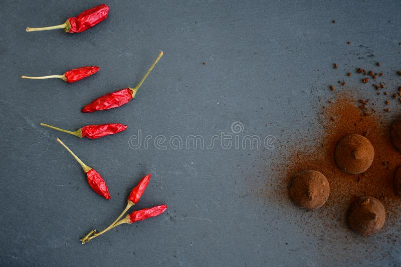 Cocoa truffles and red hot chili peppers stock photo