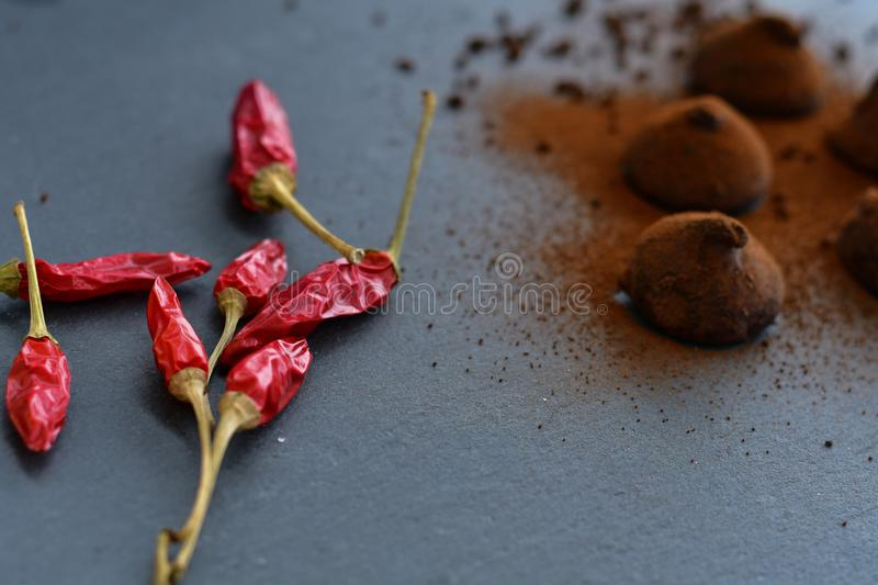 Cocoa truffles and red hot chili peppers stock photos