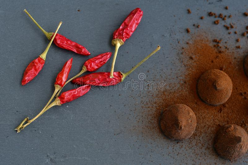 Cocoa truffles and red hot chili peppers stock images