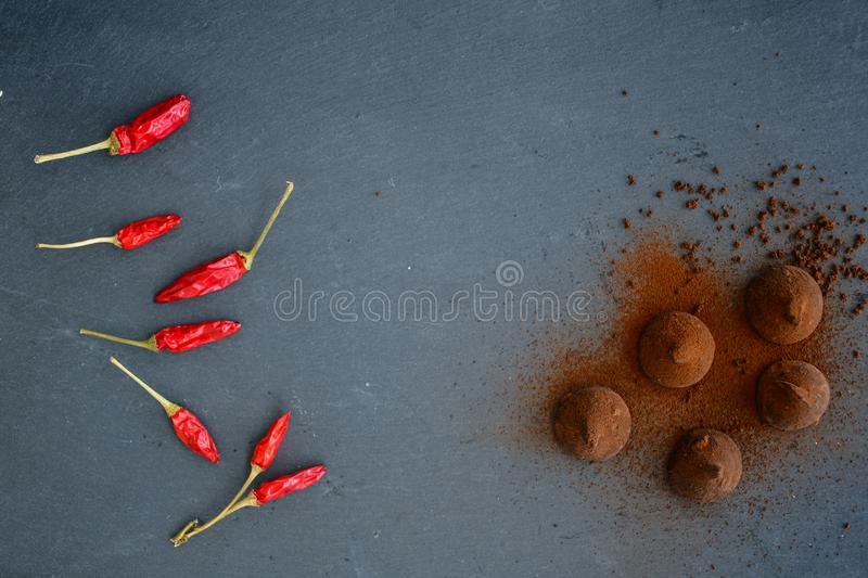 Cocoa truffles and red hot chili peppers stock photography