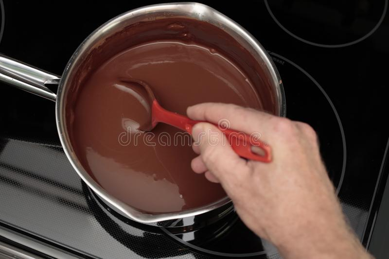 Cocoa Water Being Stirred with an Adult Male Hand w a Red Spoon royalty free stock photography