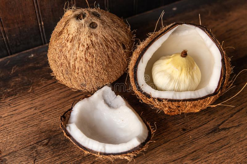 Coconut Apple. Inside rich fatty healthy saturated fats coconut on wooden rustic table royalty free stock image