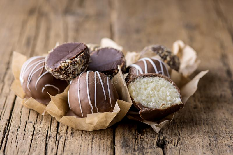 Coconut Balls Being Covered with Carob or Chocolate on Wooden Baclground Raw Vegan Dessert Healthy Diet Dessert Tasty Candy stock photo