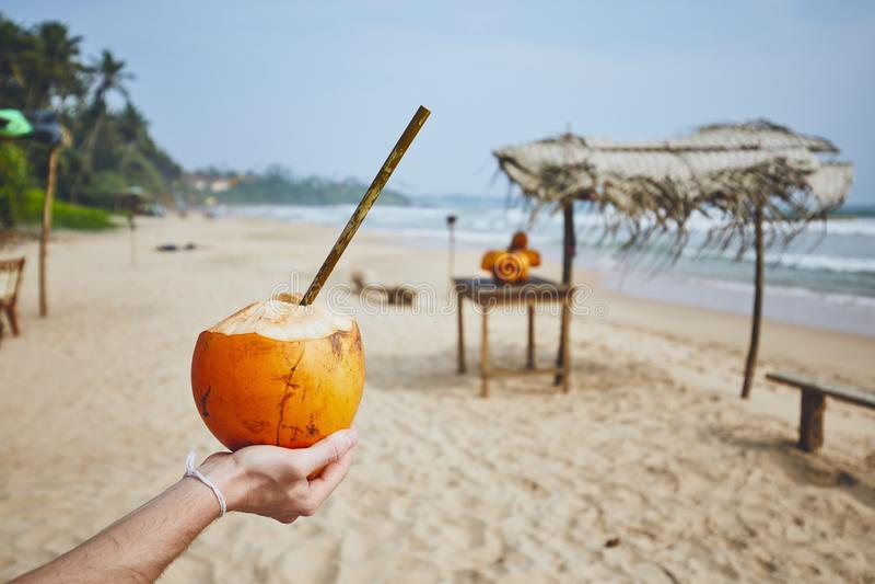 Coconut with bamboo straw. Hand of young man holding coconut with bamboo straw. Refreshment on the beach. Matara, Sri Lanka stock images