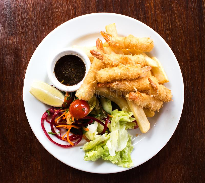 Coconut battered prawn shrimps served with hot chips and salad on white plate stock photography