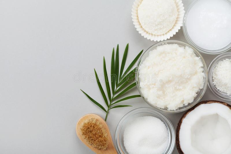 Coconut body scrub with ingredients on gray table top view. Homemade cosmetic for peeling and spa care. Flat lay. Coconut body scrub with ingredients on gray stock photo