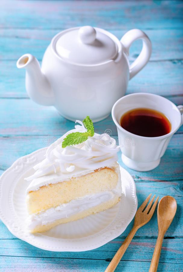 Coconut cake decorated with coconut meat and mint leaf on a white plate, With a tea of ready-to-drink and a teapot placed on a stock photo