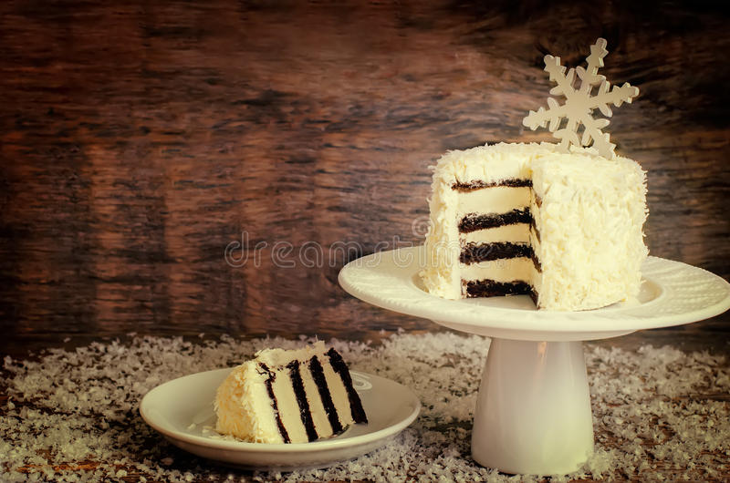 Coconut chocolate cake with cream cheese. Coconut chocolate cake with butter cream on a dark wood background. tinting. selective focus on a snowflake stock photos