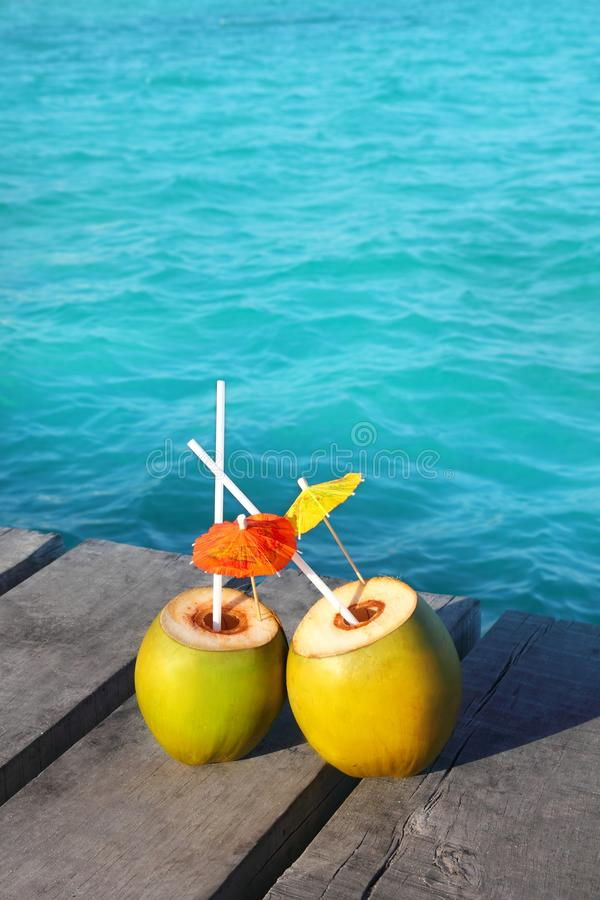 Coconut coktails in caribbean on wood pier royalty free stock photo